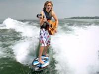 Auf dem Surfbrett Gitarre spielen und singen