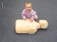 Baby macht Herzdruckmassage und Beatmung