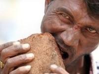 Mann isst Backsteine und Kies