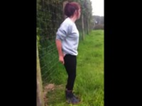 Nackten Hintern an elektrischen Zaun halten